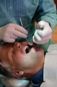 The dentist surgically secures the metal implant into the patient's jaw bone.